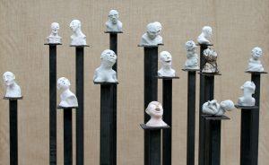 Sonja Schumacher, Köppe, 2014, 15x Keramikskulpturen, 13-18 cm hoch, 10-15 cm breit, auf Eisenstel